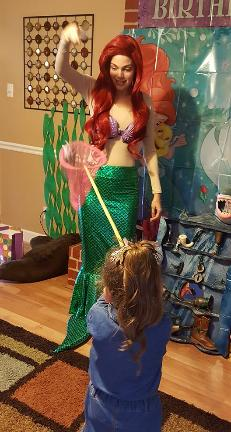 Princess Ariel ( the Little Mermaid) celebrates at a birthday party costumed character in Houston, Texas.